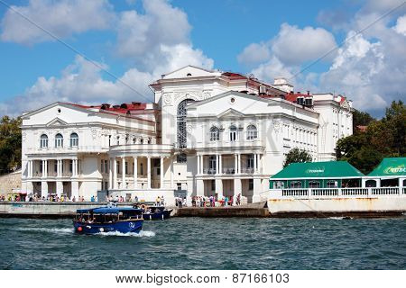 SEVASTOPOL, CRIMEA. UKRAINE - AUGUST 17, 2012: Trip boats and people against the Palace of Childhood and Youth. The house was built in 1914 for the Institute of physical methods of treatment