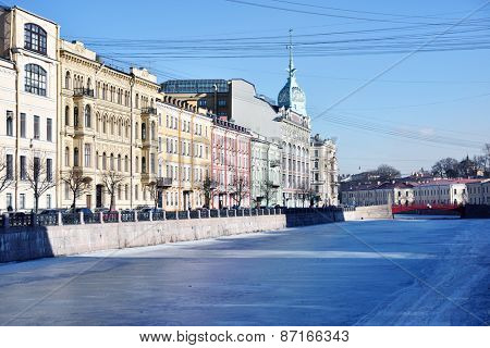 ST. PETERSBURG, RUSSIA - MARCH 5, 2015: People on the embankment of river Moyka West side of the Red bridge. The bridge was built in 1808-1813 to a design by William Heste