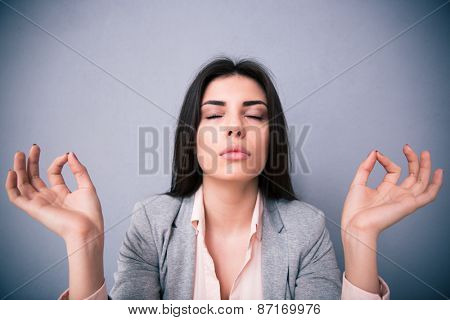 Young beautiful woman meditating with closed eyes over gray background