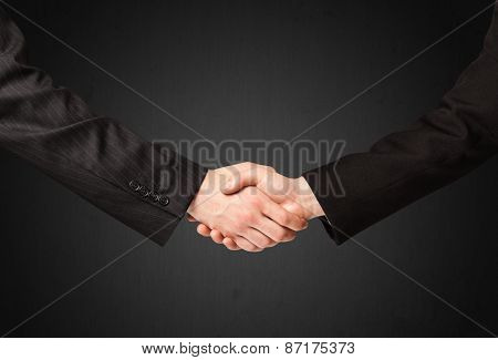 Business handshake on black background