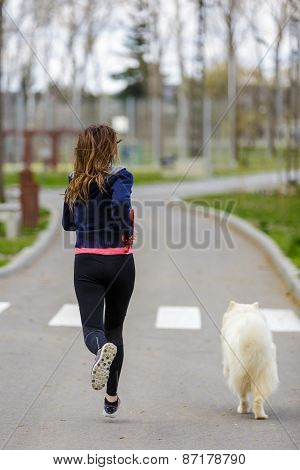 Attractive Sport Girl Running With Dog In Park
