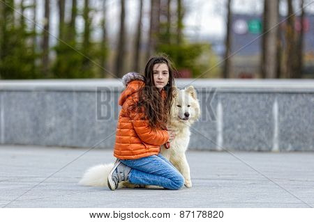 A little beautiful girl with her pet dog outdoors in park