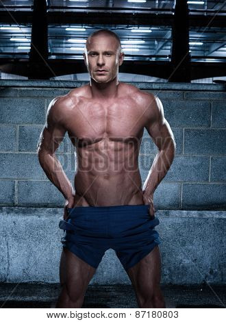 Portrait of a Gorgeous Fit Bald Young Man, Showing his Sexy Body, Standing in a Rustic Building with Both Hands on his Waist and Looking at the Camera.