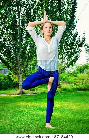 Beautiful young woman doing yoga in the summer park. Healthy lifestyle. Yoga.