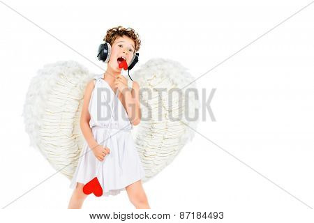 Cheerful little boy in a costume of angel listening to music in headphones and singing. Cupid. Valentine's day.