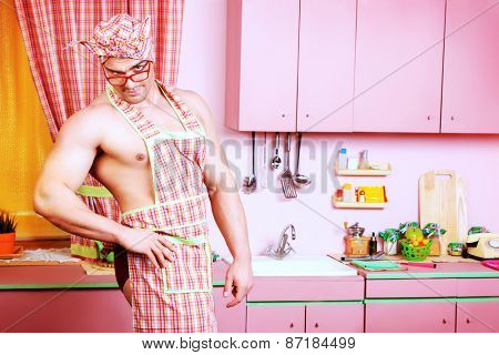 Handsome muscular man in an apron cooking in the pink kitchen. Love concept. Valentine's day.