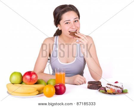 Girl Sitting Near Fruit And Sweets And Bites Chocolate
