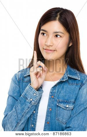 Beautiful young woman looking up with finger point upwards