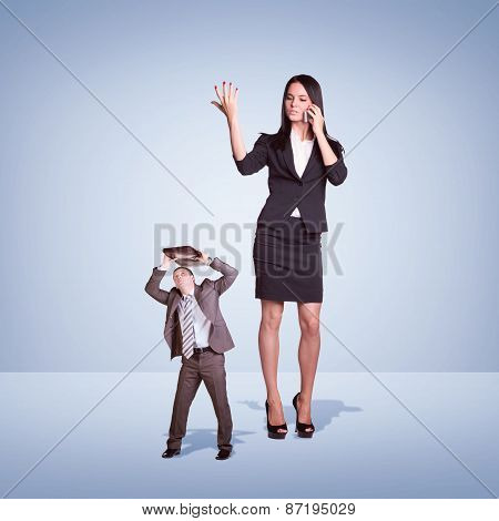 High angry girl talking on phone, small man covered briefcase