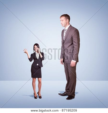 High businessman looking down at little woman using phone