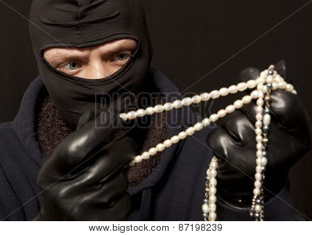 Thief. Man in black mask with a pearl necklace. Focus on thief