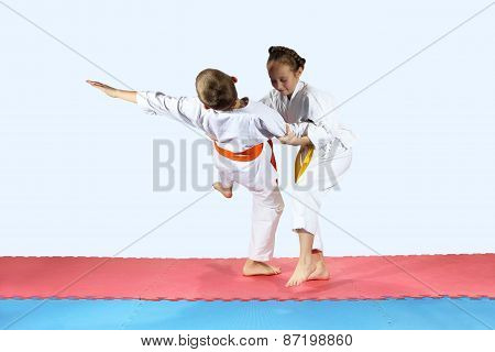 Girl in karategi throws the boy in karategi on the mat