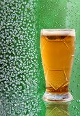 image of ice crystal  - Fresh beer glass with reflection on ice crystals and drips green background - JPG