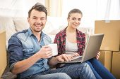 image of  habits  - The young happy couple searching for apartments with laptop - JPG