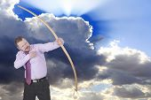picture of archery  - Businessman practicing archery with clouds in background - JPG