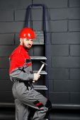 stock photo of overalls  - man wearing overalls with red helmet and hummer near brick wall - JPG