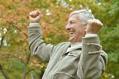 stock photo of older men  - cheerful elderly man out for a walk in the park - JPG
