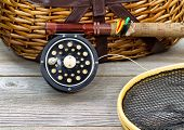 stock photo of fly rod  - antique fly fishing reel rod landing net creel and artificial flies on rustic wood - JPG
