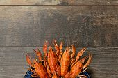 foto of carapace  - Plate of red crayfishes on old dark wooden table in bottom part - JPG