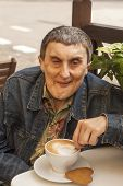 stock photo of disability  - Elderly disabled man with cerebral palsy sitting at outdoor cafe with cup of coffee - JPG