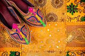 foto of shoes colorful  - Colorful ethnic shoes on yellow Rajasthan cushion cover on flea market in India - JPG