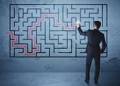stock photo of maze  - Businessman finding the solution of a maze - JPG