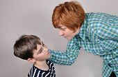 stock photo of scared  - Woman scolding and pulling the ear of the scared young boy - JPG