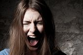 stock photo of terrifying  - Terrified young woman keeping eyes closed and shouting while standing against dark background - JPG