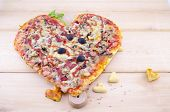 stock photo of olive shaped  - Heart shaped pizza and home made heart shaped pastry on wooden table - JPG