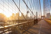 stock photo of brooklyn bridge  - Couple walking on pedestrian path across Brooklyn bridge - JPG