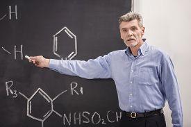 image of professor  - Professor of chemistry writes on the blackboard formula in University - JPG