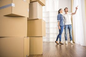foto of packing  - The young happy couple looking around their new apartment - JPG