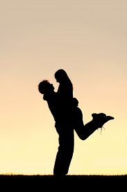 stock photo of lifting-off  - A silhouette of a happy young couple hugging with the man lifting the woman off of her feet at sunset - JPG