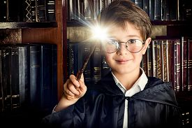 picture of fairy  - A boy stands with magic wand in the library by the bookshelves with many old books - JPG