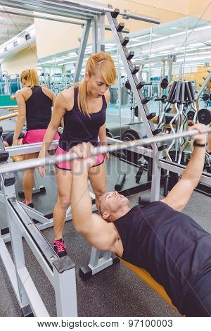 Woman coach screaming to man in bench press training