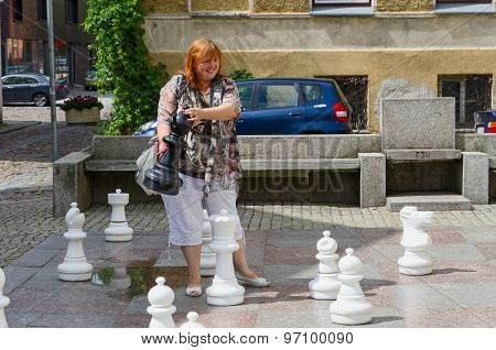 Young Cheerful Woman Holds Big Chess Piece On Street In Old Town Of Klaipeda