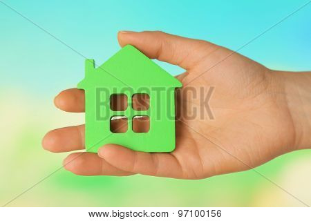 Female hand with model of house on blurred background