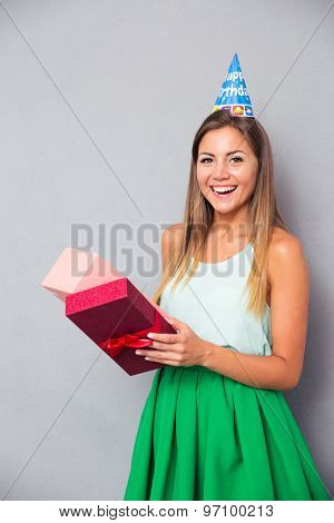 Laughing young girl opening gift box over gray background. Looking at camera