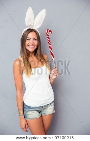 Smiling young girl with rabbit ears holding lollipop over gray background. Looking at cmaera