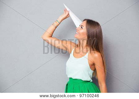 Smiling young girl holding paper plane over gray background