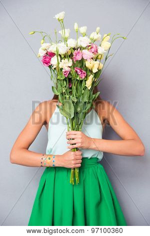 Portrait of a young woman covering her face with flowers on gray background