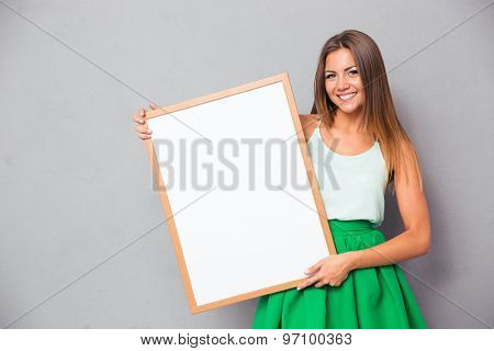 Happy girl holding blank board over gray background and looking at camera
