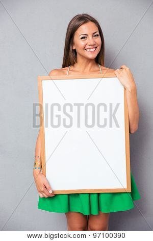 Smiling young woman holding blank board over gray background