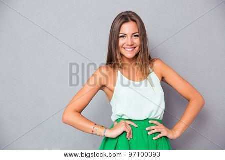 Portrait of a smiling cute woman standing over gray background and looking at camera