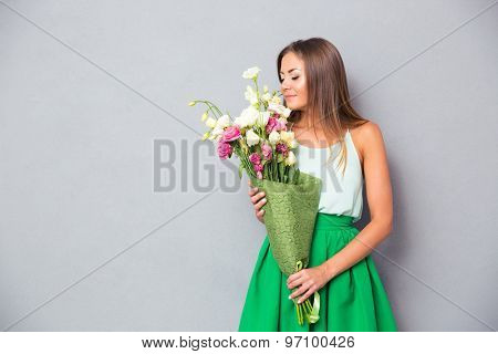 Portrait of a young beautiful woman smelling flowers over gray background