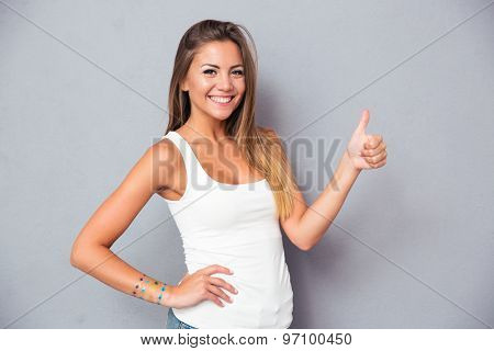 Portrait of a smiling young woman showing thumb up over gray background. Looking at camera
