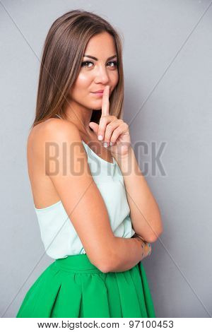 Portrait of a pretty young woman showing finger over lips on gray background. Looking at camera