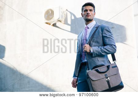 Portrait of a confident businessman standing outdoors near office building