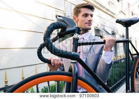 Happy businessman carrying his bicycle on city streets