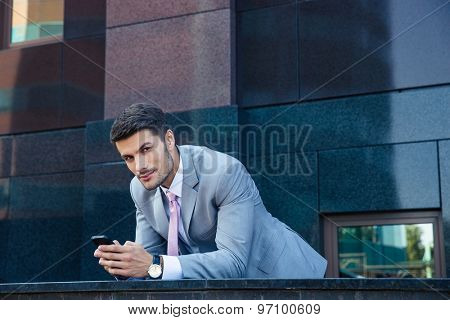 Serious businessman using smartphone outdoors and looking at camera